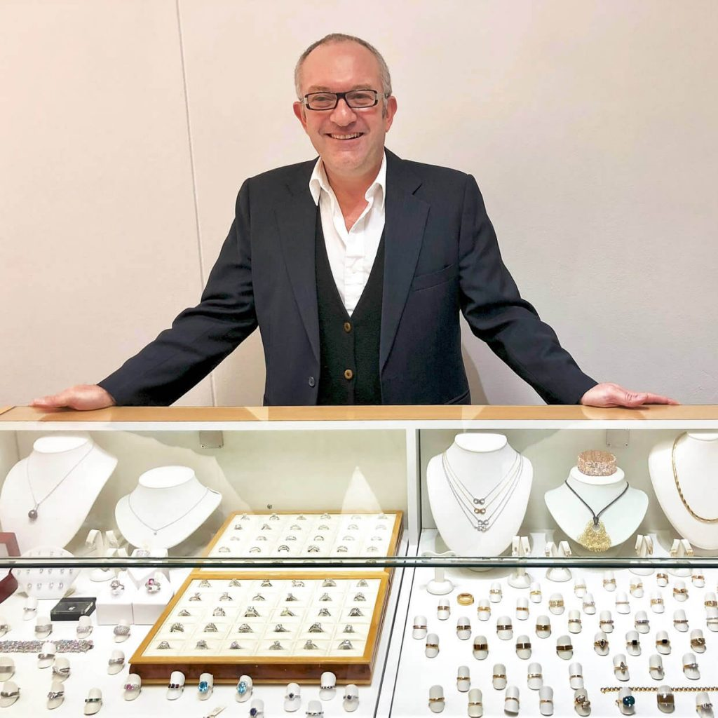Photo of Mark Nathan the jewellery designer standing next to a display which features rings, diamonds, necklaces and pendants